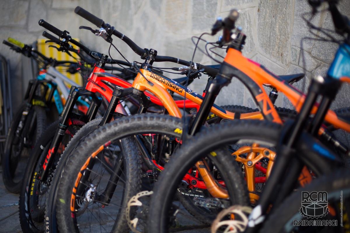 Diverse mountain bike in fila al sole ad asciugare dopo il lavaggio di fine giornata.