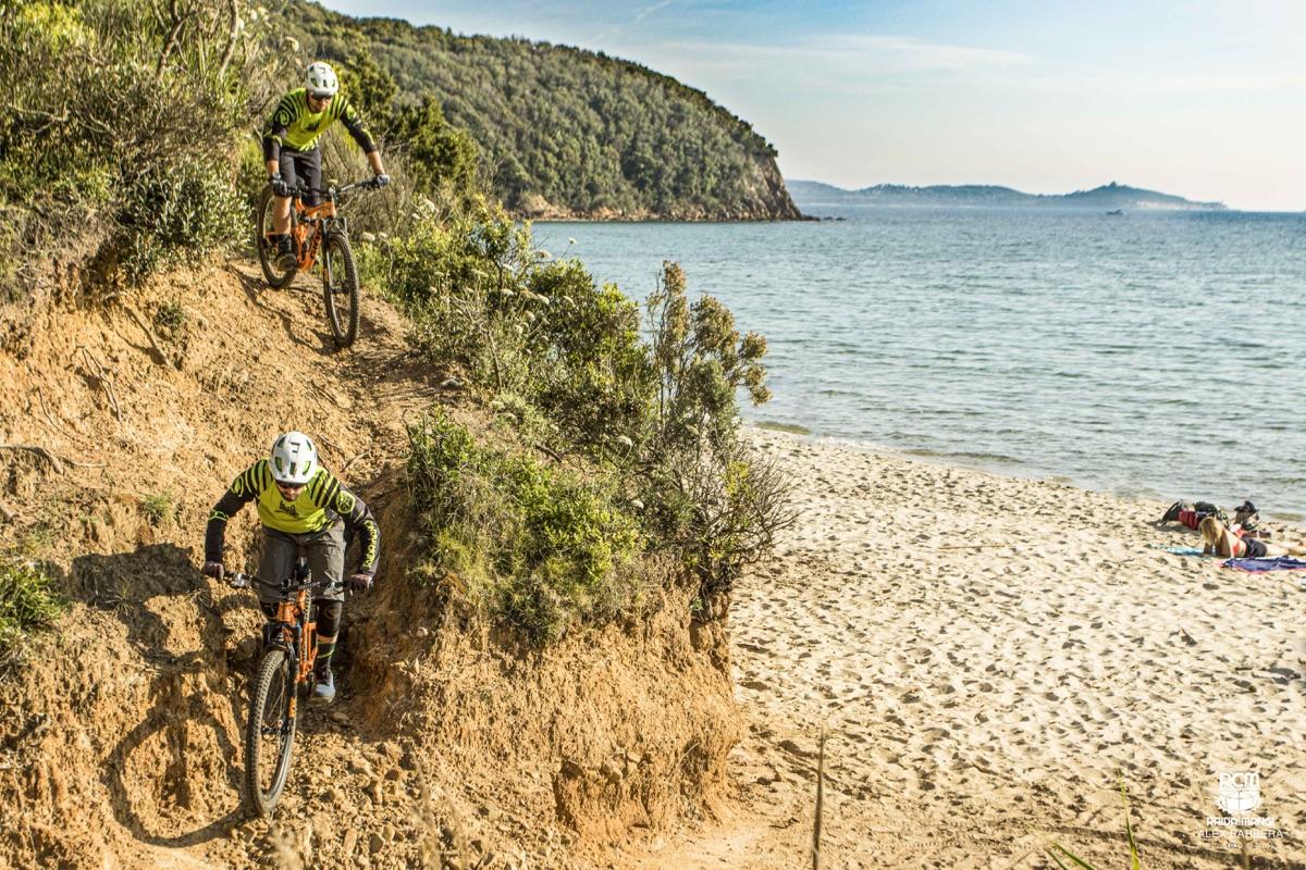 Due mountain biker percorrono un sentiero in fuoristrada fino in riva al mare.