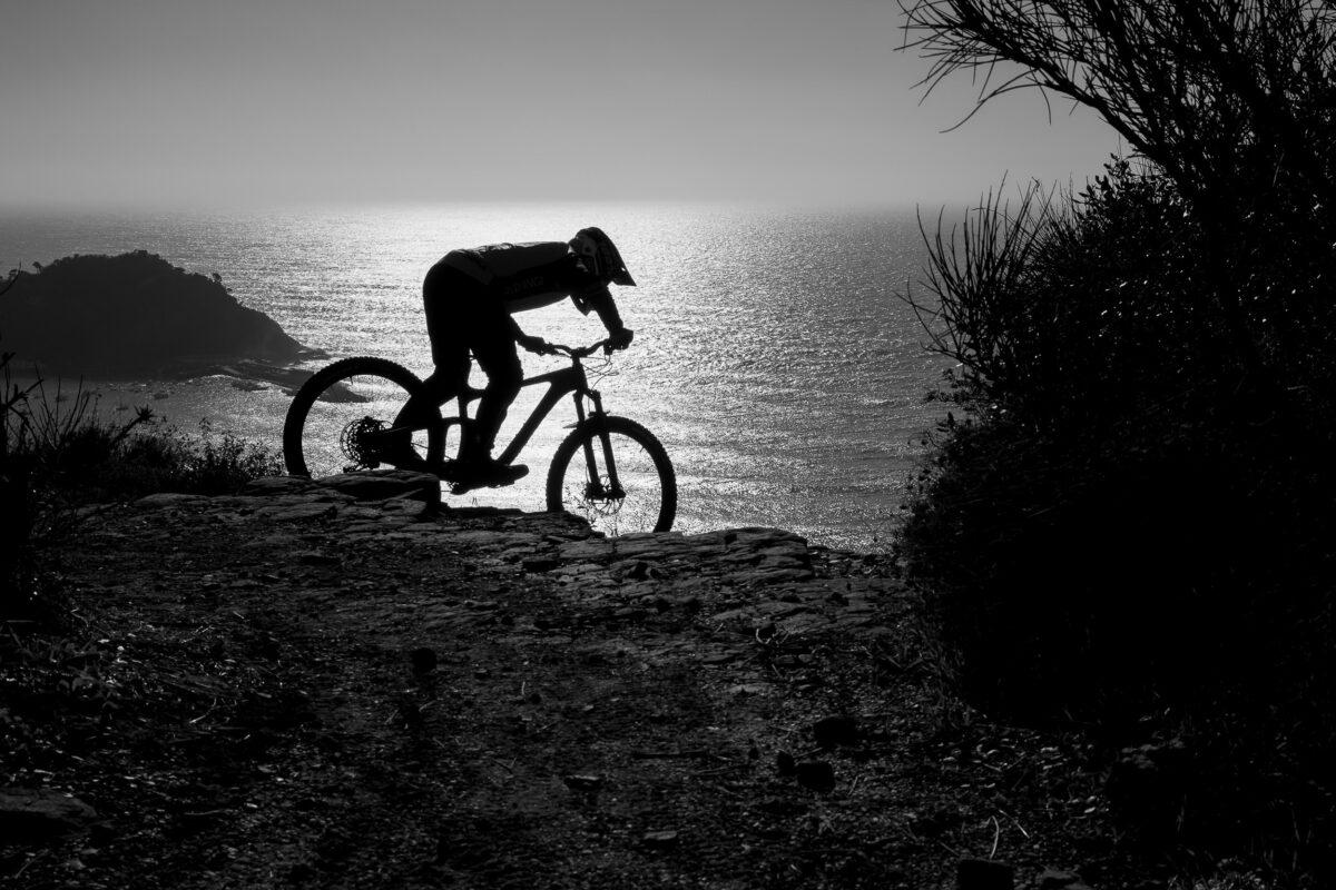 Un biker in sella alla sua mountain bike percorre un sentiero al tramonto con il mare sullo sfondo.